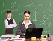 Teacher sitting at the desk Stock Photo