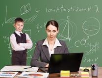 Teacher sitting at the desk Stock Images