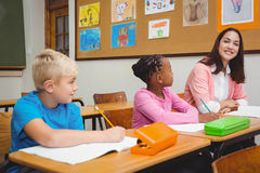 Teacher sitting with her students Stock Photography