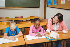 Teacher sitting with her students Royalty Free Stock Photography