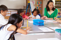 Teacher sitting with kids in elementary school lesson stock photo