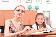 Teacher sitting near pupil Stock Photo