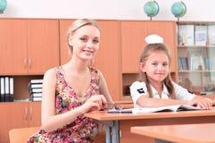 Teacher sitting near pupil Royalty Free Stock Photography
