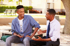 Teacher Sitting Outdoors Helping Male Student With Work. Looking At Each Other Smiling Stock Photo