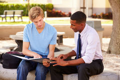 Teacher Sitting Outdoors Helping Male Student With Work. Looking At Folder Stock Photo