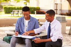 Teacher Sitting Outdoors Helping Male Student With Work. Pointing At Folder Whilst Sitting Down Stock Photos