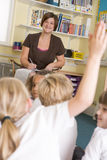 A teacher sitting with a primary class Stock Photo