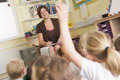 A teacher sitting with a primary class Stock Photos