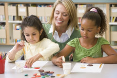Teacher sitting with students in art class, Stock Images