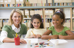 Teacher sitting with students in art class stock photos