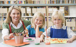 Teacher sitting with students in art class Stock Images