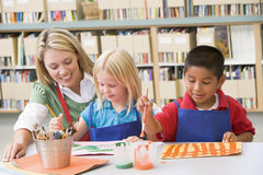 Teacher sitting with students in art class Stock Photography