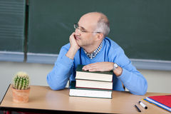 Teacher sitting thinking at his desk. Attractive male teacher sitting thinking at his desk staring off to the side with his hand resting on a pile of textbooks Royalty Free Stock Photo