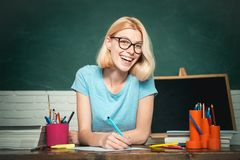 Teacher is skilled leader. Young teacher in glasses over green chalkboard background. Beautiful teacher in classroom stock photo