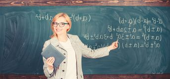 Free Teacher Smart Woman With Book Explain Topic Near Chalkboard. School Teacher Explain Things Well And Make Subject Royalty Free Stock Images - 168395679