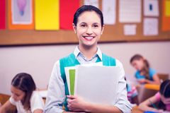 Teacher smiling at camera in classroom Stock Image