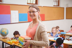 Teacher smiling at camera while holding stack of notebooks Royalty Free Stock Photo