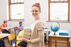 Teacher smiling at camera while holding stack of notebooks Royalty Free Stock Photography