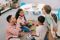 teacher with soap bubbles and multicultural preschoolers sitting on floor with colorful bricks royalty free stock image