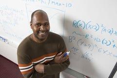 Teacher Solving Math's Equations On Whiteboard. High angle portrait of confident teacher solving math's equations on whiteboard in classroom Stock Photos