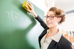 Teacher with a sponge in front of a school class Royalty Free Stock Image