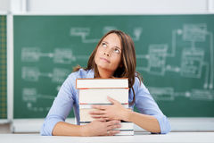Teacher With Stack Of Books Looking Up At Classroom Desk Stock Images