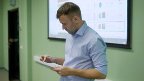Teacher standing alone in front of class of students and touching his pad while students are doing practical work. Young stock footage