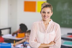 Teacher standing with arms crossed in classroom stock image