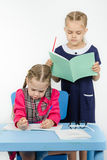 Teacher standing behind the pupil looks notebook Stock Photography