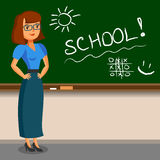 Teacher standing on blackboard background in the classroom.  Royalty Free Stock Photo
