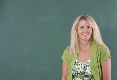 Teacher standing by chalkboard Stock Photo