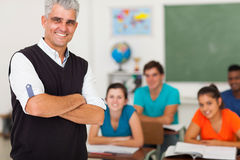 Teacher standing class. Smiling middle aged high school teacher with arms folded standing in front of the class Stock Image