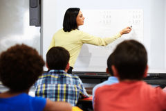 Teacher Standing In Class Using Interactive Whiteboard. With Students Sitting At Desk Stock Photo