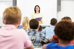 Teacher Standing In Front Of Class Of Pupils Stock Photo