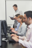 Teacher standing in front of computer class Royalty Free Stock Photos