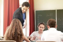 Teacher teaching or educate at the board a class in school. Teacher standing while math lesson in front of a blackboard and educate or teach students or pupils stock photos