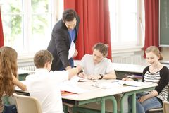 Teacher teaching or educate at the board a class in school. Teacher standing while math lesson in front of a blackboard and educate or teach students or pupils royalty free stock photography