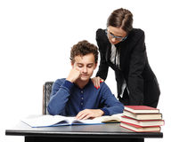 Teacher standing next to student's desk with hand on his shoulde Stock Photography