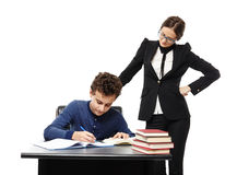 Teacher standing next to student's desk with hand on waist, supe Stock Photos