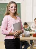 Teacher standing with notebook in classroom royalty free stock photo