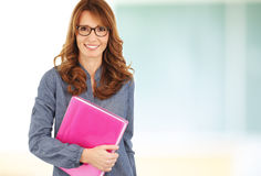 Teacher standing with notebook in classroom Royalty Free Stock Images