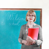 Teacher. Stands at blackboard with folder in hands. Welcome to school is written royalty free stock image