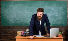 Teacher strict serious bearded man lean on table chalkboard background. Teacher looks threatening. Rules of school
