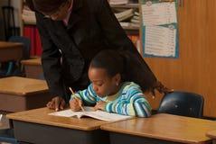 Teacher an student. A teacher helping a student with a lesson stock photos