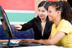 Teacher and student. Female chinese teacher and african american student in classroom royalty free stock photography
