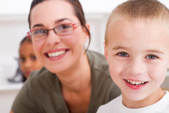 Teacher and student. Close-up of a happy young preschool teacher and cute young preschool boy in classroom Stock Image
