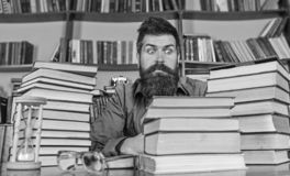 Teacher or student with beard sit at table with hourglass and glasses, defocused. Bookworm concept. Man on shocked face. Sit between piles of books, while royalty free stock photos