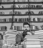 Teacher or student with beard sit at table with hourglass and glasses, defocused. Bookworm concept. Man on strict face. Sit between piles of books, while royalty free stock image