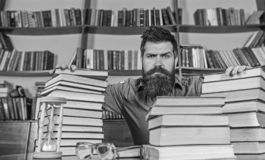 Teacher or student with beard sit at table with hourglass and glasses, defocused. Man on strict face sit between piles. Of books, while studying in library stock photos