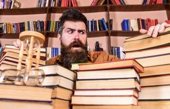 Teacher or student with beard sits at table with books, defocused. Bibliophile concept. Man on confused face between. Piles of books, while studying in library royalty free stock photo